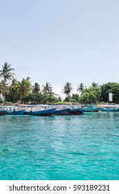 A harbor with a lot of boats near the palms in azure water of Indian ocean