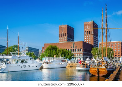 Harbor with boats and wooden yacht with town hall in Oslo, Norway