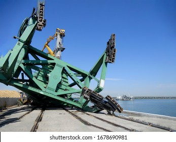 Harbor Crane collapse. Fallen port crane after a strong storm. A large-capacity harbor crane lies on the pier. The process of investigating an incident at a commercial port.