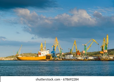 Harbor cranes on the blue sky background in Feodosia, Crimea, Russia. Panoramic view of cranes with yellow booms from the sea. Industrial scenery of harbor. Panorama of heavy cranes in sunlight.