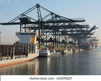 Harbor cranes unloading containers from ships on a sunny morning in the port of Antwerp.