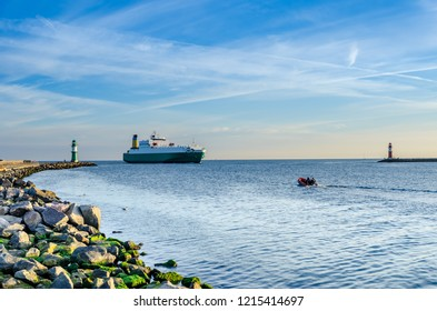 harbor entrance in Warnemünde-Rostock with incoming ferry and lighthouse