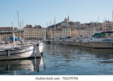 harbor in the fench city of marseille with blue sky on a sunny day and the church notre dame de marseille on the hills