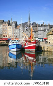 Harbor of Honfleur with the old pier, the Lieutenance house and 2 fishing boats, Normandy, France