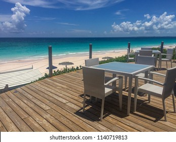 Harbor Island, Bahamas. Pink Sand Beach. Beautiful ocean view with sand.  Blue Turquoise water and green grass. White table and chairs on a wooden floor.