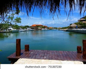 Harbor / marina in Puerto Aventuras with boats, popular coastal town in Riviera Maya, Mexico as seen from wooden pier through straw on sunny day