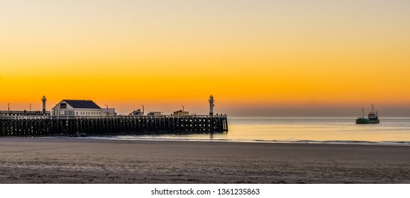 the harbor pier at the beach of blankenberge, Belgium, a boat sailing in the sea, beautiful sunset and colorful sky