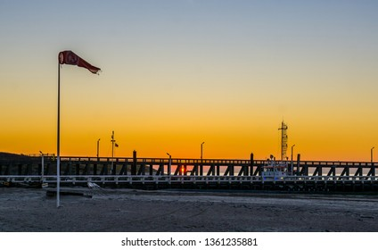 the harbor pier with a wind flag at the beach of Blankenberge, Belgium, colorful sunset