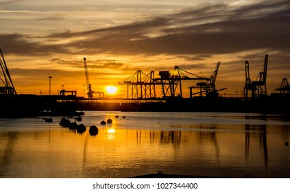 harbor sunrises red colors in the sky and water reflection many load cargo cranes port skyline ready to load containers on ships Transport and logistics, export, merchandise