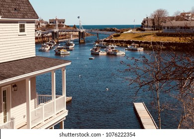 A harbor view shot of Perkins Cove in Ogunquit, Maine with a footbridge and fishing boats.
