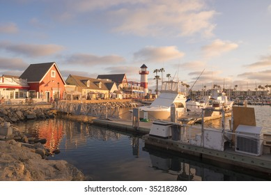 Harbor - wharf with bright red and orange buildings, red and white light house at end of wharf, boats docked in harbor, palm trees, blue sky with white fluffy clouds.
