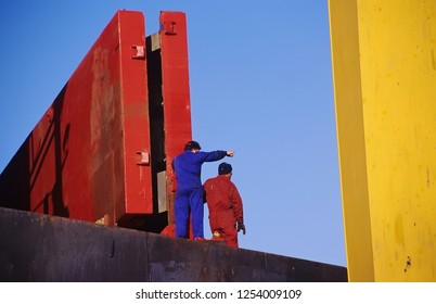 Harbor workers over container ship deck.