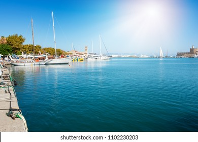 Harbor with yachts and sail boats in front of medieval City of Rhodes (Rhodes, Greece)