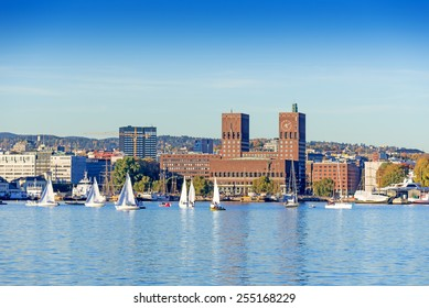 Harbour with boats and wooden yacht with town hall on background at sunset in Oslo, Norway