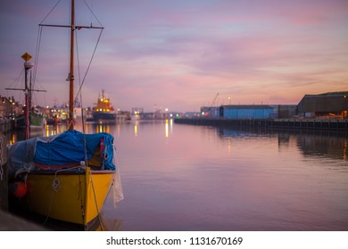 Harbour lights. Soft landscape image of river port quay at dusk. Tranquil harbor scene of quayside boats and shipping from the fishing town of Great Yarmouth, England, UK.