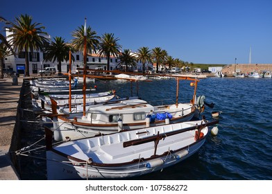 Harbour promenade with boats and palm trees in Fornells town, Menorca, Balearic Islands, Spain