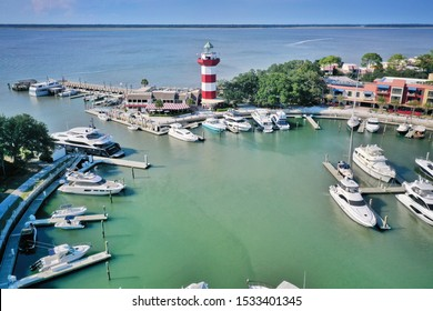 HARBOUR TOWN, HILTON HEAD ISLAND, SC, USA - SEPTEMBER 2019: Aerial view of boats moored in the marina and a lighthouse on the pier