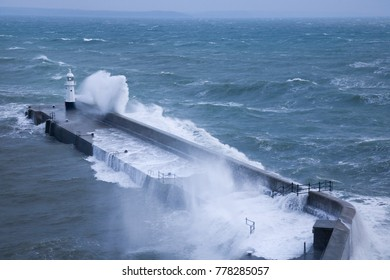 Harbour wall and lighthouse beaten by rough waves at Mevagissey in Cornwall, UK.