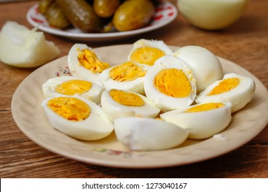 Hard boiled chicken eggs in a porcelain plate on vintage wooden table