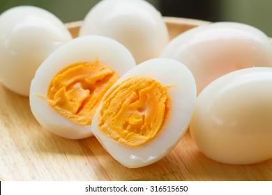 Hard boiled eggs, sliced in halves on wooden background
