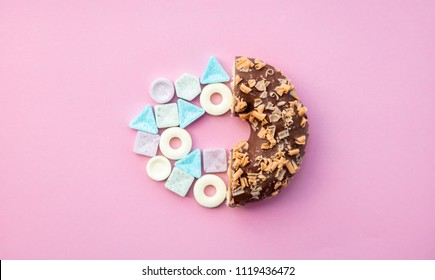 hard candy and chocolade donut on pink background. Above view
