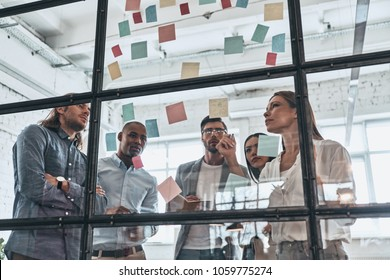 Hard choice to make. Group of young modern people in smart casual wear using adhesive notes while standing behind the glass wall in the board room
