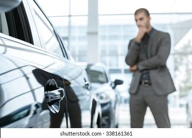 Hard choice. Selective focus on a car, man choosing car on the background