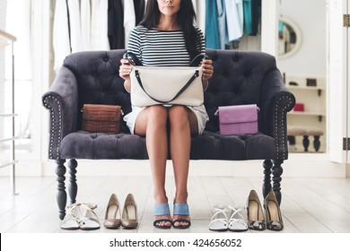 Hard to choose the perfect pair. Part of beautiful young woman holding leather purse while sitting on sofa at the shoe store