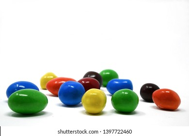 Hard, colorful shelled chocolate candy with a peanut center on a white background