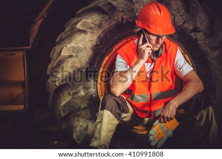 Hard Construction Business Concept with Caucasian Businessman Making Business Call While Seating Inside Heavy Duty Bulldozer Tire.