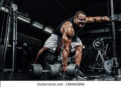 Hard Core Bodybuilding. Bodybuilder ready to lift heavy dumbbell