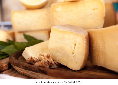 Hard cow cheese on the wooden board decorated with dried figs