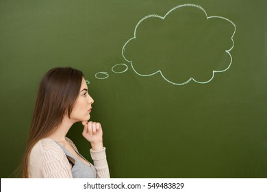 Hard decision. Profile shot of an attractive young girl thinking with her hand to her chin blank thought bubble on chalkboard near her head thoughtful wisdom planning dreaming imagination wish concept