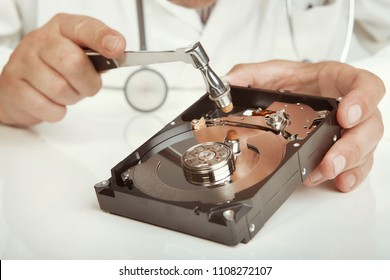 Hard disc drive doctor checking condition of opened 3,5'' drive with hammer