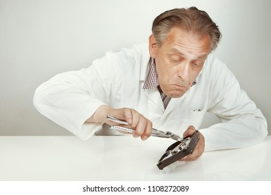 Hard disc drive specialist erasing data from hard disc drive with pliers