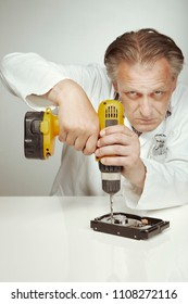 Hard disc drive specialist erasing data from hard disc drive with drill