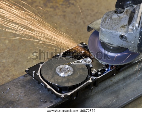 hard disk drive with rotating grinder and sparks in front of rusty back