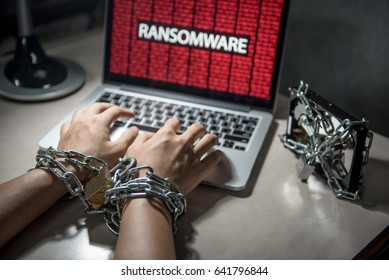 Hard disk file locked with monitor show ransomware cyber attack internet security breaches on computer laptop, user hand tied up by chains and lock concept