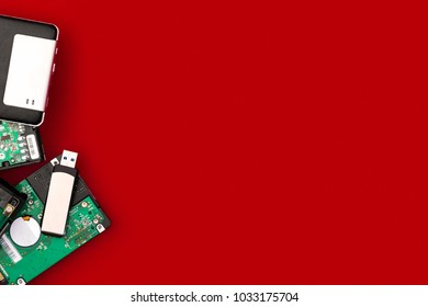 Hard drives and flash drive on the side of the frame on a red background. Top view with space for your text. Computer storage concept.