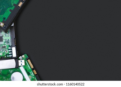 Hard drives and flash drive on the side of the frame on a black background. Top view with space for your text. Computer storage concept.