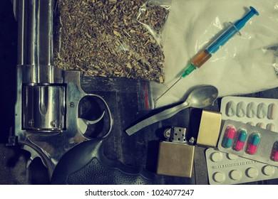 Hard drugs and gun revolver on dark table. A dark theme, drug use. White powder, marijuana, heroin, hard drugs, lighter and a spoon with pills.