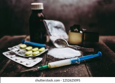 Hard drugs on dark table. A dark theme, drug use. White powder, heroin, hard drugs, lighter and a spoon with pills.