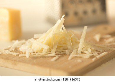 Hard grated cheese for cooking on a cutting board on a white background