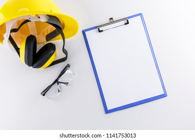Hard hat, earmuffs, safety goggles and a clipboard on a white background
