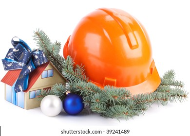Hard hat, fir-tree branches, Christmas toys and small house on a white background.