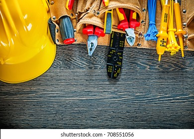 Hard hat leather tool belt on wooden board electricity concept.