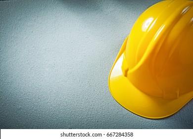 Hard hat on concrete background construction concept.