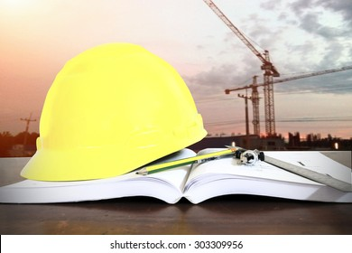 hard hat with pencil compasses and rulers/book on table at construction site background