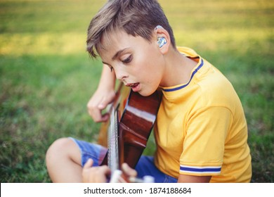 Hard of hearing preteen boy playing guitar and singing. Child with hearing aids in ears playing music and singing song in park. Hobby art activity for children kids. Authentic childhood moment.
