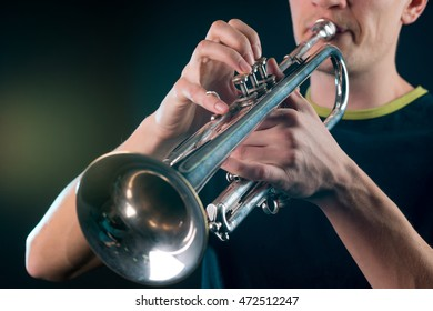 Hard process of playing the vintage trumpet with the man blowing out the air into the tube and meanwhile pressing the buttons of the musical instrument.
